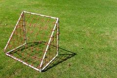 Mini klein voetbaldoel voor kinderen met rode netto op green royalty-vrije stock afbeeldingen