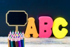 Mini lápices de madera de la etiqueta y del colorante de la pizarra sobre fondo de la pizarra Fotos de archivo