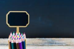 Mini lápices de madera de la etiqueta y del colorante de la pizarra sobre fondo de la pizarra Imagenes de archivo