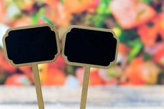 Mini labels en bois de tableau noir au-dessus du fond végétal de salade Photo libre de droits