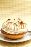 Mini lemon meringue cake. With cream top and silver fork on plate, shot on a light wooden background Stock Photography