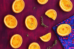 Mini lemon tarts with thyme on deep lilac background Stock Image