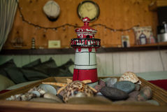 Mini lighthouse. In wooden plate with sea stones and shels Stock Image