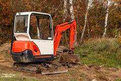 Mini máquina escavadora em um terreno de construção Trabalho da escavação A máquina escavadora funciona no jardim Foto de Stock