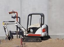 Mini máquina escavadora em uma construção da construção Imagem de Stock
