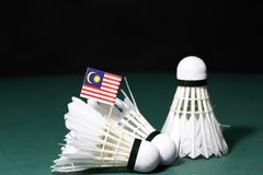 Mini Malaysia flag stick on the heap of used shuttlecocks on green floor of Badminton court. With dark black background stock photos