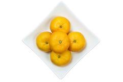 Mini Mandarin Oranges. On white dish isolated on white background Stock Photos