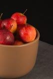 Mini manzanas en taza en fondo negro Imagenes de archivo