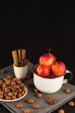 Mini manzanas en taza y nueces en fondo negro Fotografía de archivo libre de regalías