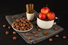 Mini manzanas y nueces en taza en fondo negro Imagen de archivo libre de regalías
