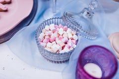 Mini marshmallows coloridos nos produtos vidreiros em uma tabela branca com laço azul Mini inchado branco e cor-de-rosa diferente Fotografia de Stock Royalty Free
