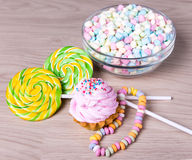 Mini marshmallows in glass bowl, candies and cup cake on wooden Royalty Free Stock Photography