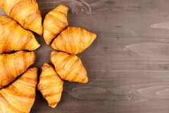 Mini and maxi croissants lying on wooden table Royalty Free Stock Photos