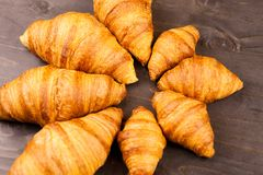 Mini and maxi croissants lying on wooden table Royalty Free Stock Photo