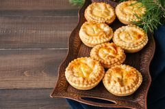Mini meat pies from flaky dough on a vintage tray over wooden ba. Ckground Royalty Free Stock Images