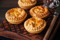 Mini meat pies from flaky dough on a vintage tray over wooden ba. Ckground Royalty Free Stock Photos