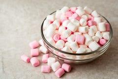 Mini melcochas blancas y rosadas en bol de vidrio en el fondo de piedra Imagenes de archivo