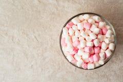 Mini melcochas blancas y rosadas en bol de vidrio en el fondo de piedra Fotografía de archivo