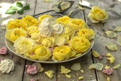 Mini Meringues de différentes couleurs et des roses jaunes Photographie stock libre de droits