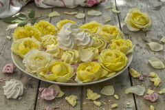 Mini Meringues of different colors and yellow roses Stock Photography