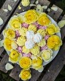 Mini Meringues von verschiedenen Farben und von gelben Rosen Lizenzfreies Stockfoto