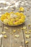 Mini Meringues von verschiedenen Farben und von gelben Rosen Stockfotos