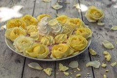 Mini Meringues von verschiedenen Farben und von gelben Rosen Stockbild