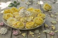Mini Meringues von verschiedenen Farben und von gelben Rosen Stockfoto