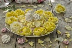 Mini Meringues von verschiedenen Farben und von gelben Rosen Stockfotografie