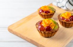 Mini mieszani owocowi tarts z pomarańczową wiśnią i kiwi na drewnianym talerzu obraz stock