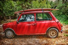 Mini Minor Mayfair with a surfboard on the roof royalty free stock image