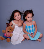 Mini Models. Two little girls sitting together on a grey background and playing model. One girl holding a stuffed toy Stock Photos