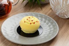 Mini mousse cake covered with yellow chocolate velour on gray pl. Ate. Modern european pastry dessert with tropical fruit flavor. Restaurant, bakery menu or Stock Image