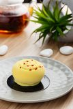 Mini mousse cake covered with yellow chocolate velour on gray pl. Ate. Modern european pastry dessert with tropical fruit flavor. Restaurant, bakery menu or Stock Photography
