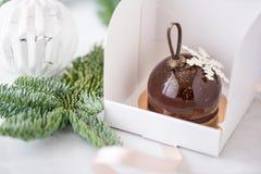 Mini mousse ciasta deser z czekoladą glazurującą Pojedynczo zawijającą w białym pudełku Gałąź świerczyna na bokeh obrazy royalty free