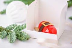 Mini mousse ciasta deser z czerwienią glazurującą Pojedynczo zawijającą w białym pudełku Gałąź świerczyna na bokeh tle fotografia stock