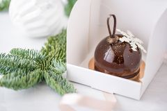 Mini mousse pastry dessert with chocolate glazed Individually wrapped in white box. The branches of spruce on bokeh royalty free stock image