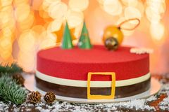 Mini mousse pastry dessert covered with red velour. Garland lamps bokeh on background. Modern european cake. French royalty free stock images