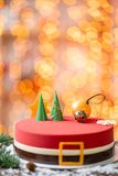 Mini mousse pastry dessert covered with red velour. Garland lamps bokeh on background. Modern european cake. French royalty free stock photos