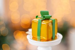 Mini mousse pastry dessert with yellow glazed. garland lamps bokeh background. In the form of gift box, ribbons of. Mini mousse pastry dessert covered with royalty free stock photography