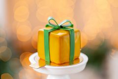 Mini mousse pastry dessert with yellow glazed. garland lamps bokeh background. In the form of gift box, ribbons of. Mini mousse pastry dessert covered with stock photography