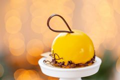 Mini mousse pastry dessert with yellow glazed on garland lamps bokeh background. Modern european cake. French cuisine. Mini mousse pastry dessert covered with royalty free stock photography
