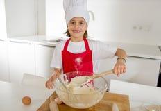 Mini muchacha del cocinero con el sombrero del cocinero y la harina y los huevos de mezcla del delantal que cuecen preparando la  Fotos de archivo