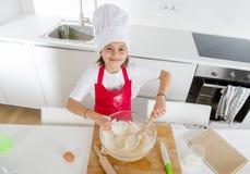 Mini muchacha del cocinero con el sombrero del cocinero y la harina y los huevos de mezcla del delantal que cuecen preparando la  Fotografía de archivo libre de regalías