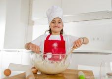 Mini muchacha del cocinero con el sombrero del cocinero y la harina y los huevos de mezcla del delantal que cuecen preparando la  Foto de archivo libre de regalías