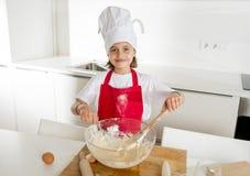 Mini muchacha del cocinero con el sombrero del cocinero y la harina y los huevos de mezcla del delantal que cuecen preparando la  Imagen de archivo