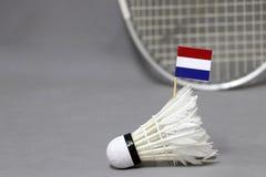 Mini Netherlands-Flaggenstock auf dem weißen Federball auf dem grauen Hintergrund und fokussieren heraus Federballschläger lizenzfreie stockbilder