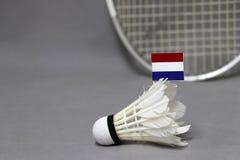 Mini Netherlands-Flaggenstock auf dem weißen Federball auf dem grauen Hintergrund und fokussieren heraus Federballschläger lizenzfreie stockfotografie