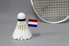 Mini Netherlands-Flaggenstock auf dem weißen Federball auf dem grauen Hintergrund und fokussieren heraus Federballschläger lizenzfreies stockbild