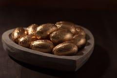 Mini ovos do chocolate, envolvidos na folha de ouro Foto de Stock